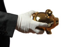 Butler with white glove an golden piggybank Stock Images