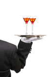 Butler with Wine Glasses on Tray. Butler in Tuxedo seen from behind with two Manhattan Cocktails on serving tray held at shoulder height vertical format over stock image
