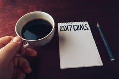 2017 buts énumèrent avec le carnet, main du ` s d'homme avec la tasse de café sur la table en bois Images libres de droits