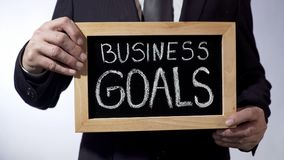 Buts d'affaires écrits sur le tableau noir, homme d'affaires tenant le signe, stratégie Photographie stock