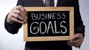 Buts d'affaires écrits sur le tableau noir, homme d'affaires tenant le signe, stratégie Photo libre de droits