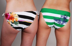 The butt of two bikini girls. Two young woman in bikinis shooing there nice round bottoms and tights Royalty Free Stock Images
