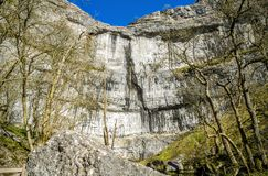 Butte at Malham Cove, North Yorkshire, England. Butte of limestone cliffs at Malham Cove in North Yorkshire, England against blue skies Royalty Free Stock Images