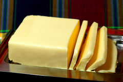 Butter. Brick of butter, slices cut, on shiny metal tray royalty free stock photo