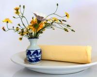 Butter auf Platte mit Vase Blumen Stockbild