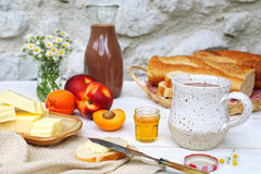 Butter, baguette, honey, fruits and chocolate milk Royalty Free Stock Photos