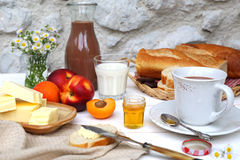 Butter, baguette, honey, fruits and chocolate milk Stock Photography