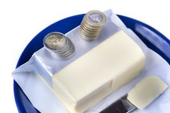 Butter on the blue plate with euro coins money on white Royalty Free Stock Image