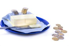 Butter on the blue plate with euro coins money on white Stock Images