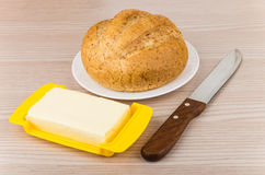 Butter, bread in plate and knife on table Stock Images