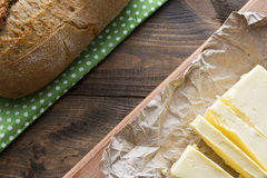 Butter and bread. Butter with bread top view lie on a wooden table Royalty Free Stock Image