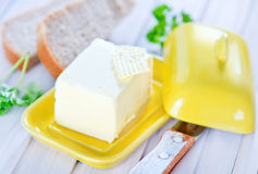 Butter. And bread on the wooden table Royalty Free Stock Images