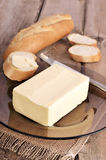 Butter and bread on wooden table Stock Images