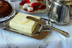 Butter in the butter-dishand and knife. On a white tablecloth royalty free stock photography