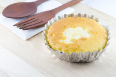 Butter cake in foil cup on wood desk Stock Image