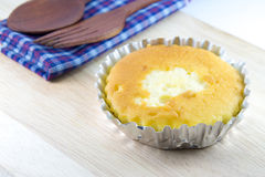 Butter cake in foil cup on wood desk Stock Photography