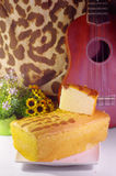 Butter cake and piece of butter cake with ukulele. Royalty Free Stock Photography