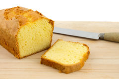 Butter cake and slice of cake on chopping board. With bread knife Stock Photography