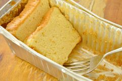 Butter cake slice and fork in aluminum tray. Butter cake slice and silver fork in aluminum tray royalty free stock photos