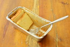 Butter cake slice and fork in aluminum tray. Butter cake slice and silver fork in aluminum tray royalty free stock images