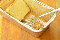 Butter cake slice and silver fork in aluminum tray. On wooden table stock image