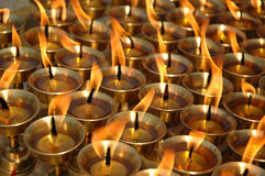 Butter Candles. Golden butter oil candles burning in a Buddhist temple Stock Images