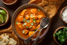 Butter Chicken Curry. A bowl of delicious indian butter chicken curry with naan bread, basmati rice, and cilantro garnish Royalty Free Stock Photography
