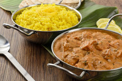 Butter Chicken & Lemon Rice. Indian butter chicken curry and lemon rice served with chapatis on a banana leaf Royalty Free Stock Images