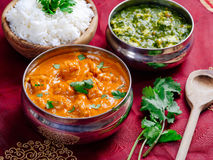 Butter chicken and Saag Paneer. Photo of an Indian meal of Butter Chicken, rice and Saag Paneer. Focus across the Butter Chicken bowl Royalty Free Stock Photo