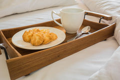 Butter cookies and coffee cup in wooden tray on comfortable bed Royalty Free Stock Photography