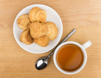 Butter cookies in white saucer, teaspoon and tea on table Stock Photos