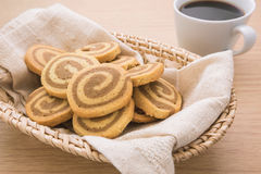 Butter cookies in wicker basket and coffee cup, filtered image Stock Photography