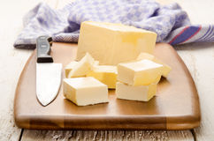 Butter cubes and kitchen knife on a wooden board Stock Image