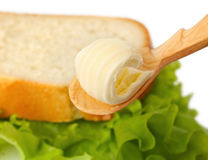 Butter curl on spoon with bread on background Stock Photos