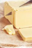 Butter cutting by knife. Piece of butter on paper cutting by knife royalty free stock image