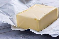 Butter in der offenen Verpackung Stockbilder