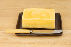 Butter dish knife. Block of butter with a knife in a dish on a wooden board Royalty Free Stock Photo
