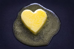 Butter heart melting. A heart shaped butter pat melting on a non-stick surface Stock Photography