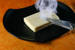 Butter and a hot knife. A dish with butter and a hot knife Stock Photo