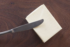 Butter and knife. Butter block on wooden background Stock Photo
