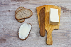 A butter knife and bread. On the wooden background Stock Photography
