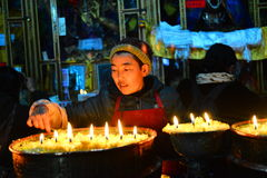 Butter lamps and Tibetan famale Royalty Free Stock Image