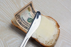 Butter and money on a slice of bread. And knife Royalty Free Stock Photos