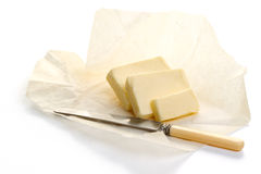 Butter on paper and knife Royalty Free Stock Images