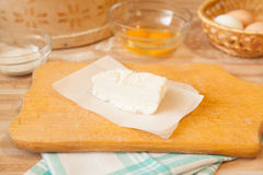 Butter on parchment on cutting board. And towel, eggs, raw eggs, salt on background on light wooden table Stock Photography