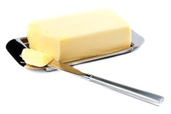 Butter. Piece of Butter on Silver Plate with Knife Royalty Free Stock Images