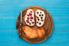 Butter sandwiches on healthy wholewheat bread topped with fresh raspberries, currants and raisins. Top view. Still life. Space for text Stock Photos