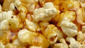 Butter sauce pours on popcorn. Butter sauce poured on golden popcorn macro shot stock video footage