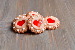 Butter shortbread cookies with red jelly in the form of hearts on the brown wooden table. Royalty Free Stock Image