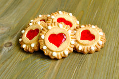 Butter shortbread cookies with red jelly in the form of hearts on the brown wooden textured table. Stock Photos